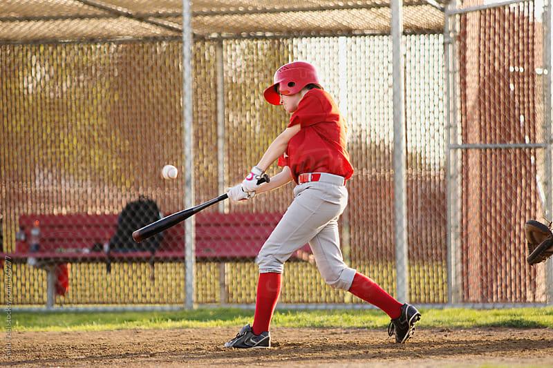 A girl batting hits the baseball in a baseball game by Tana Teel for Stocksy United