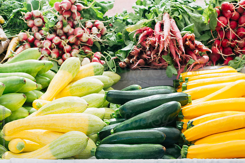 Fresh squash and produce for sale in farmers market stall by Kristin Duvall for Stocksy United