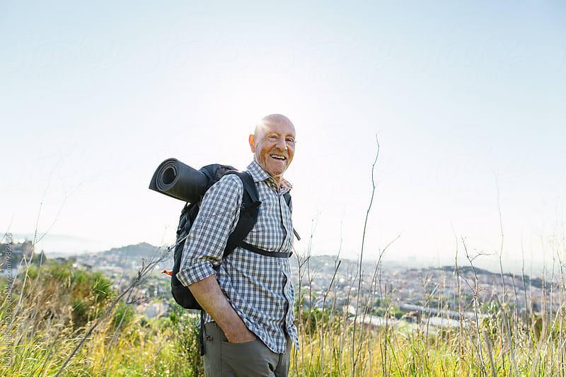 Portrait of a smiling senior man hiking on a mountain over the city. by BONNINSTUDIO for Stocksy United