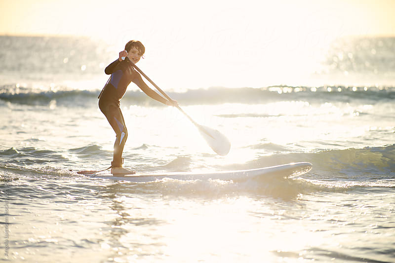 Boy riding a wave on a stand up paddle board at sunset by Angela Lumsden for Stocksy United