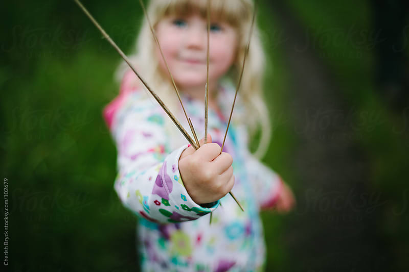 A little girl holds straw in her hands. by Cherish Bryck for Stocksy United