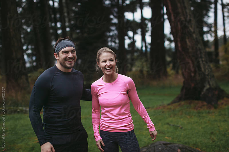 Two fit caucasian friends smiling in workout clothes outside by Rob and Julia Campbell for Stocksy United
