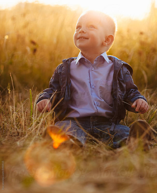 Baby boy sitting on meadow grass on sunset laughing by Ilya for Stocksy United