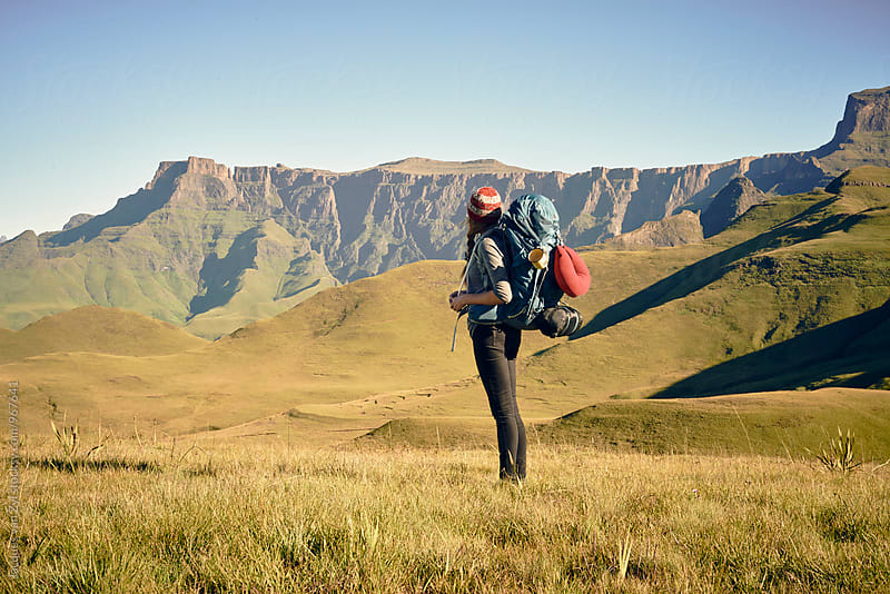 Female hiker viewing the journey ahead, standing at the base of a mountain by Jacques van Zyl for Stocksy United