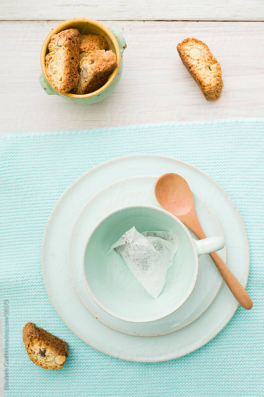 Light turquoise cup with a teabag on a plate and biscotti on the side by Elisabeth Coelfen for Stocksy United