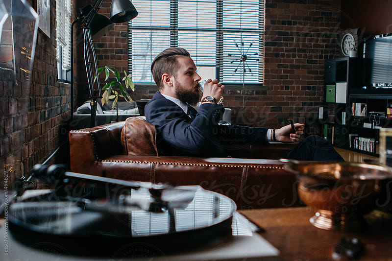 Young man drinks while sitting by record player by Jesse Morrow for Stocksy United