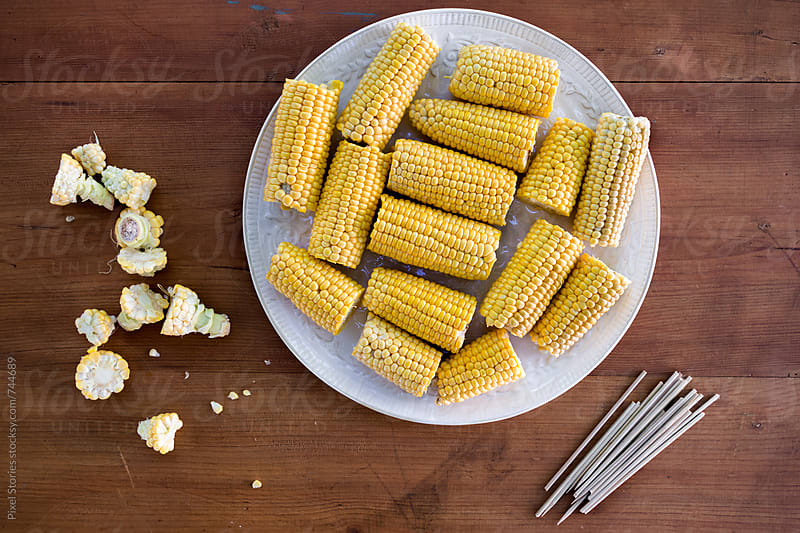 Preparing corn on the cob for a barbecue by Pixel Stories for Stocksy United
