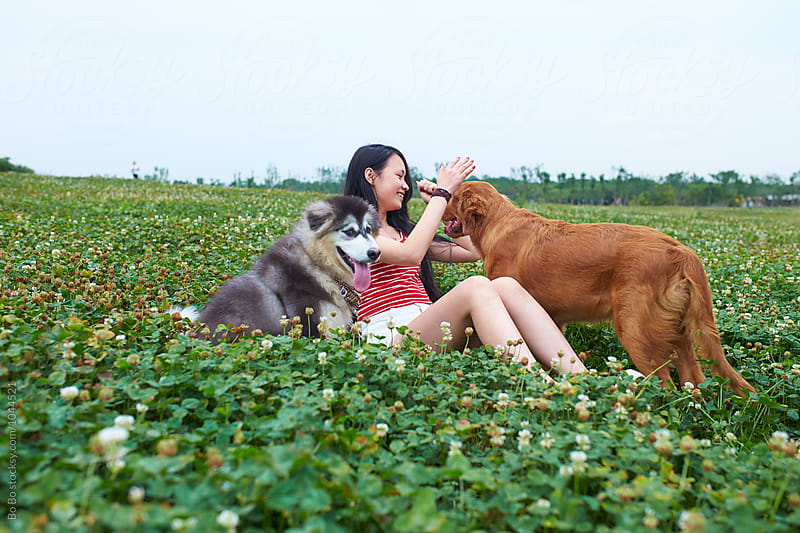 happy little asian girl with her dog outdoor by cuiyan Liu for Stocksy United