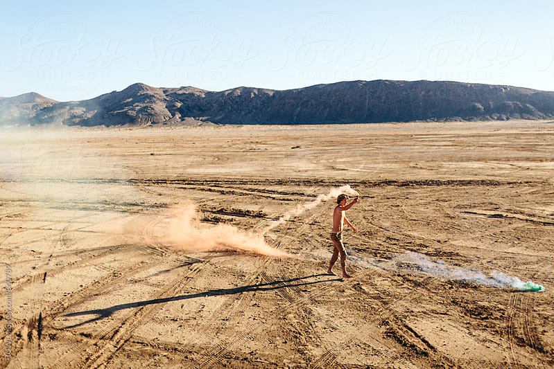 Young man running with Fireworks in the desert  by HOWL for Stocksy United