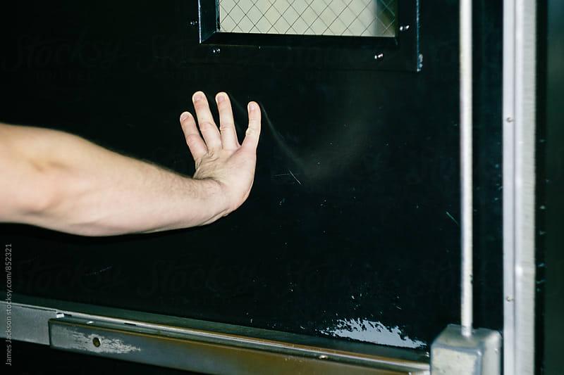 Caucasian hand opening metal door. by James Jackson for Stocksy United