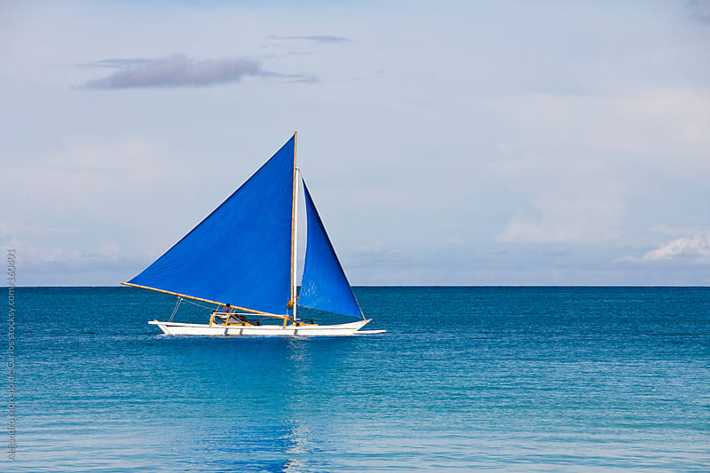 Blue sailboat on turquoise sea by Alejandro Moreno de Carlos for Stocksy United