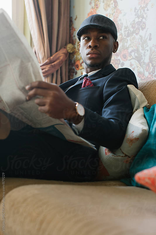 Fashionable Young Black Man Sitting in Stylish Living Room and Looking Away by VISUALSPECTRUM for Stocksy United