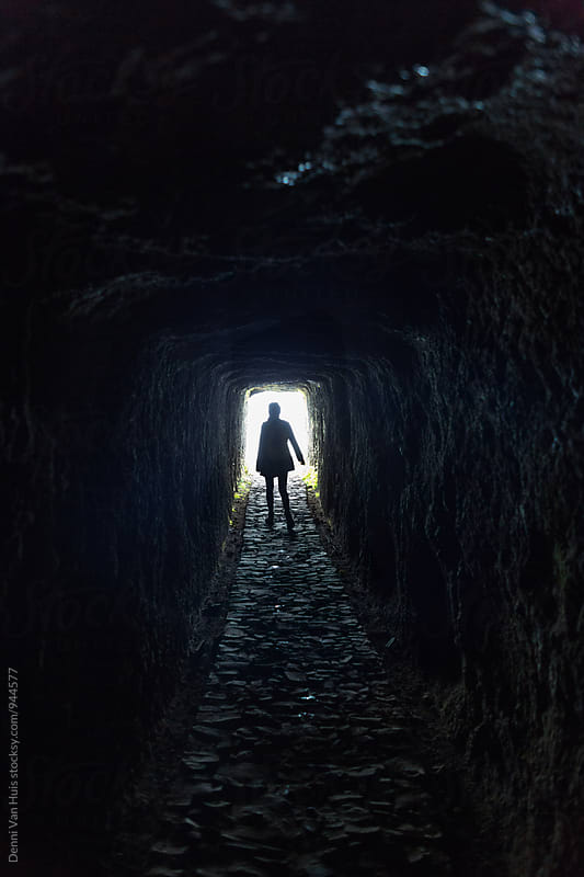 Brave woman walking through a dark tunnel in the mountains by Denni Van Huis for Stocksy United