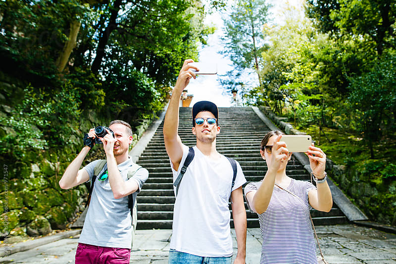 Portrait of tourist friends taking photos.  by BONNINSTUDIO for Stocksy United