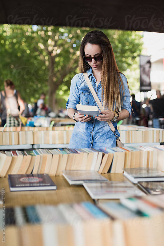 Young woman looking for a book in a market by Mauro Grigollo for Stocksy United