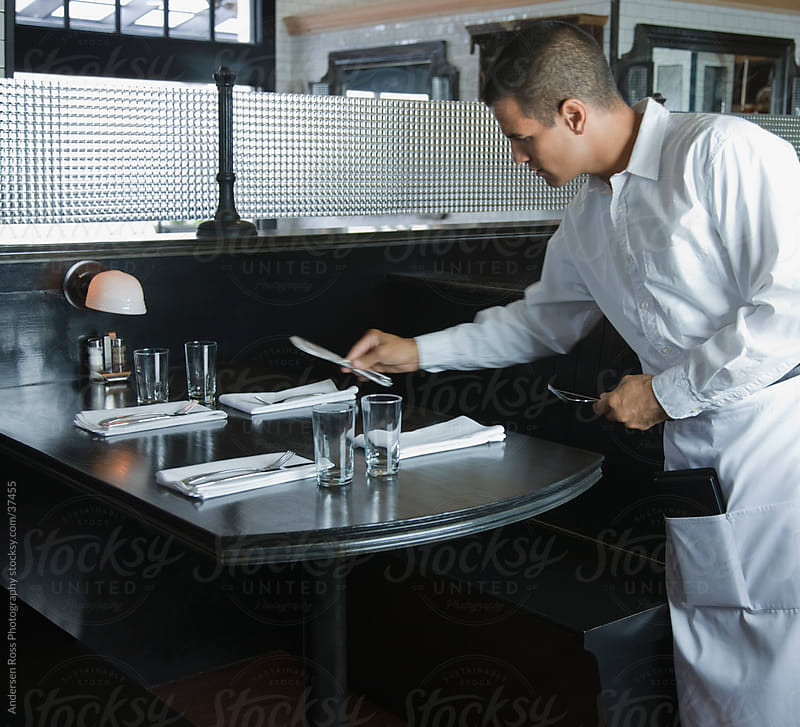 Waiter arranging table in restaurant by Andersen Ross Photography for Stocksy United