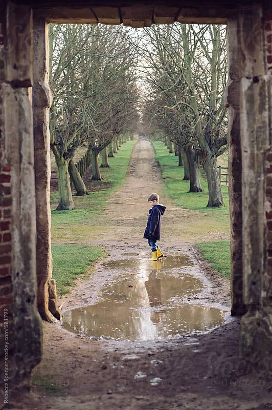 Child standing in puddle by Rebecca Spencer for Stocksy United