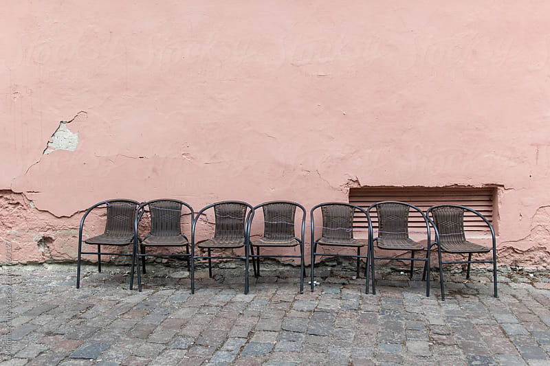 Row of empty chairs before a pink wall by Melanie Kintz for Stocksy United