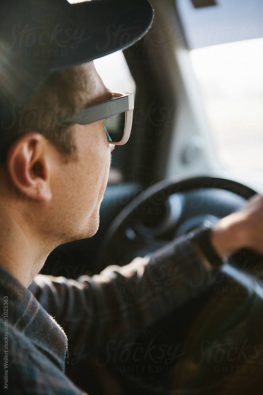 Man wearing sunglasses driving a car by Kristine Weilert for Stocksy United
