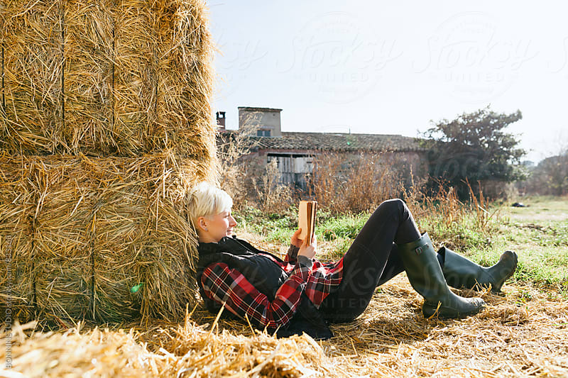 Woman resting on haystack on farm. by BONNINSTUDIO for Stocksy United