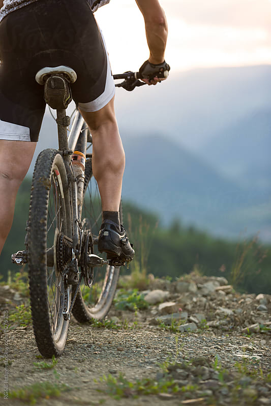 Closeup of a muscular man riding a mountain bike by RG&B Images for Stocksy United