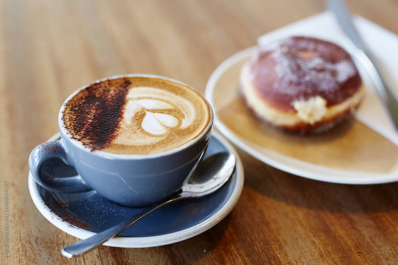 Close-up of aromatic cappuccino with donut by Martí Sans for Stocksy United