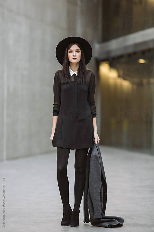 A beautiful brunette dressed in a black uniform holding her coat by Ania Boniecka for Stocksy United