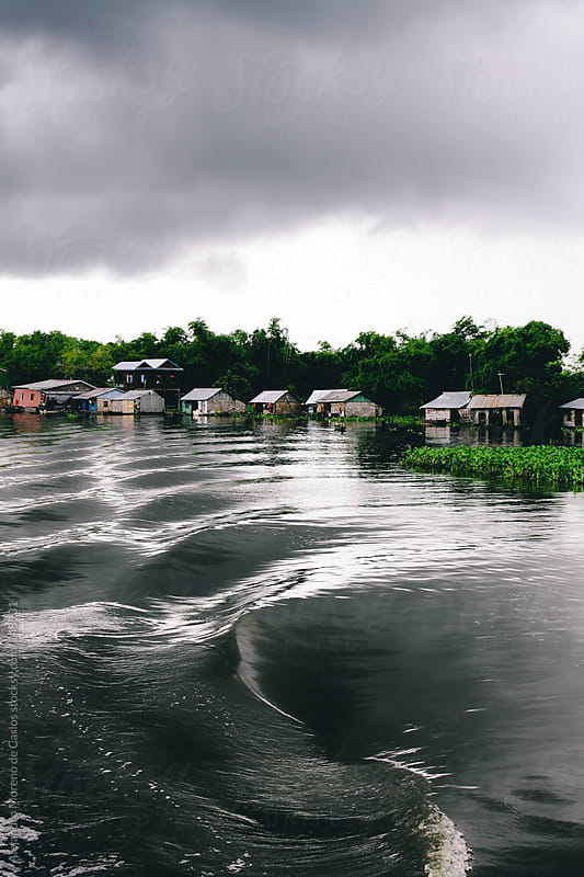 Storm in lake with dark water with floating houses. Tonle Sap lake, Cambodia by Alejandro Moreno de Carlos for Stocksy United
