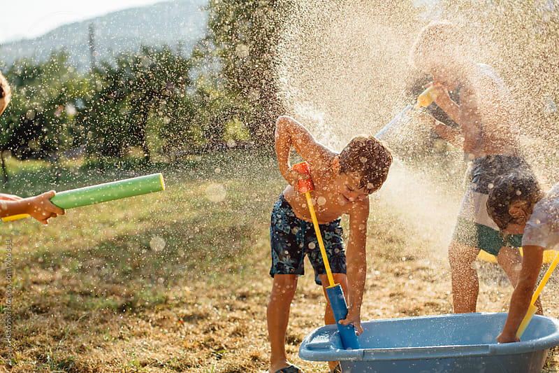 Children playing with water outdoors by Dejan Ristovski for Stocksy United