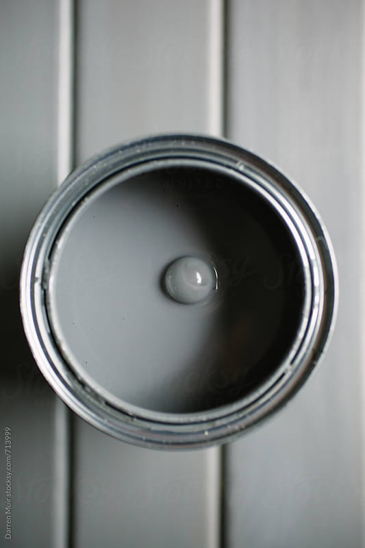 Tin of open grey paint on a grey background.  by Darren Muir for Stocksy United