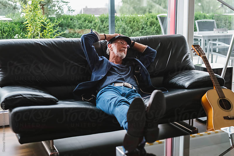Happy and serene senior man relaxing at home by Simone Becchetti for Stocksy United