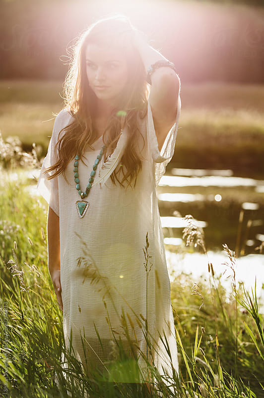 young woman walking in the grass by Shaun Robinson for Stocksy United