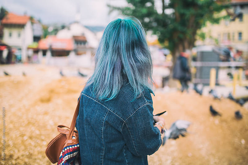 Beautiful young woman with blue hair taking photos in the city by Maja Topcagic for Stocksy United