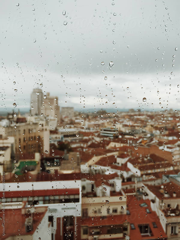 Mobile phone capture of rainy Madrid, Spain through a window glass.  by Kristen Curette Hines for Stocksy United