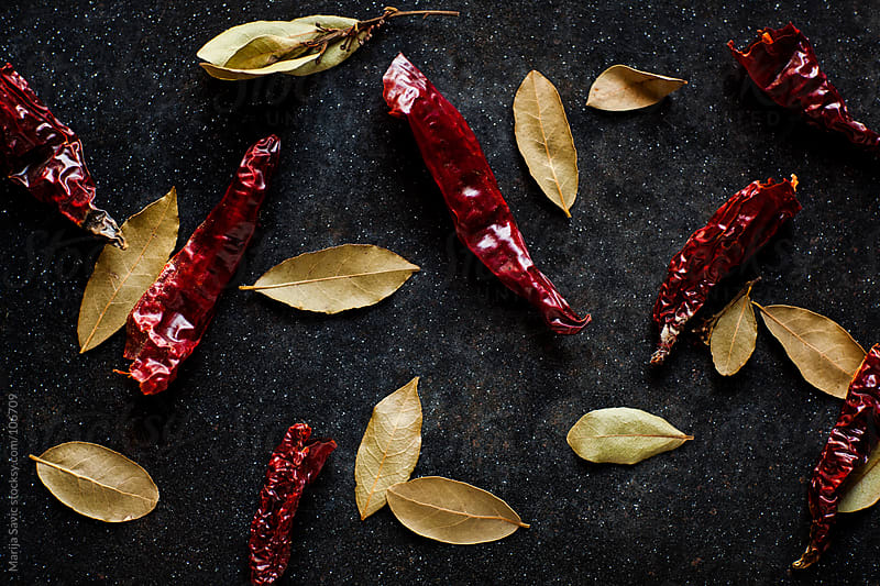 Dried chilli and bay leaf on a metal plate. by Marija Savic for Stocksy United