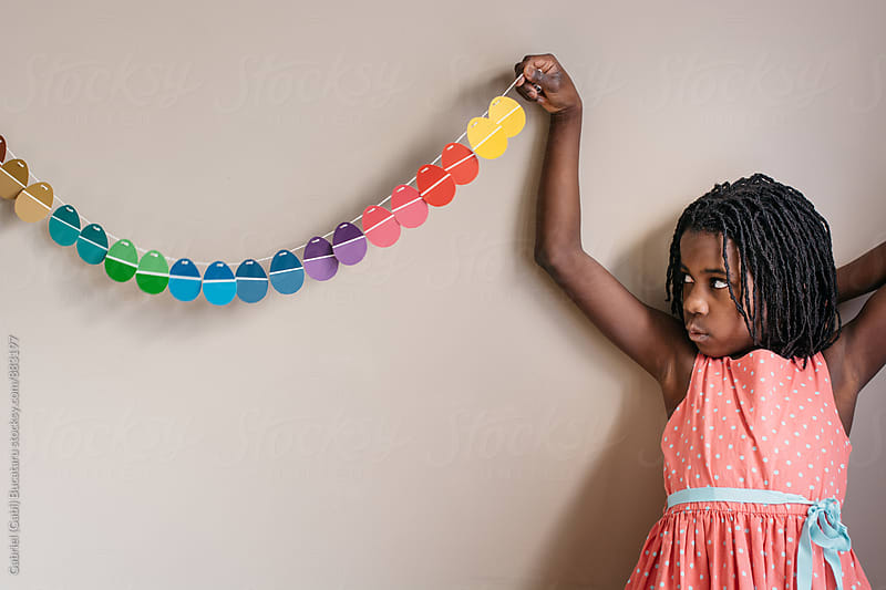 Black girl holding an end of an Easter egg banner on a wall by Gabriel (Gabi) Bucataru for Stocksy United