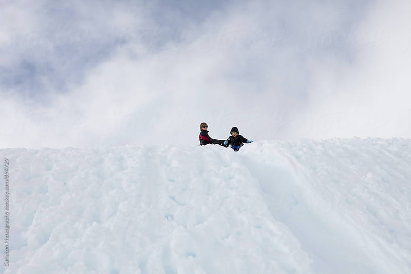 Two boys on a snowy ridge against a backdrop of clouds by Carleton Photography for Stocksy United