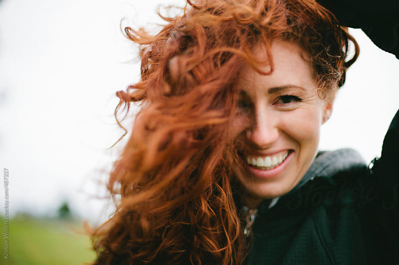 Smiling Woman with Red Curly Hair by Kristine Weilert for Stocksy United