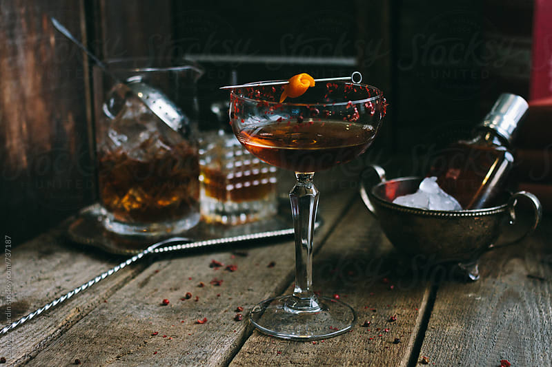 classic manhattan cocktail with orange peel and red pepper rim on wooden board by Leander Nardin for Stocksy United