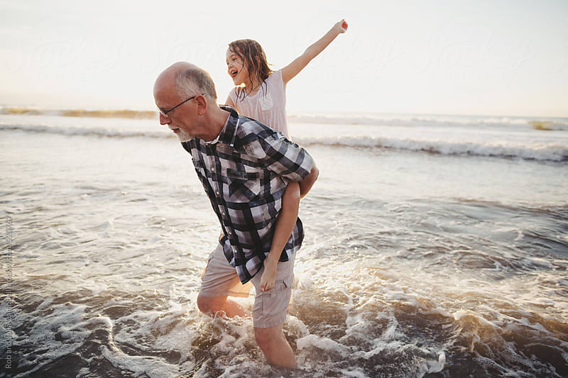 Fun, energetic grandpa playing in waves with young grandchild - girl - on beach at sunset - shoulder ride by Rob and Julia Campbell for Stocksy United