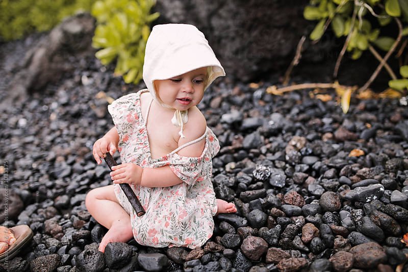 Cute baby holding a stick on the beach by Treasures & Travels for Stocksy United