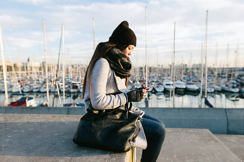 Side view of a woman using her phone sitting by the seaport. by BONNINSTUDIO for Stocksy United