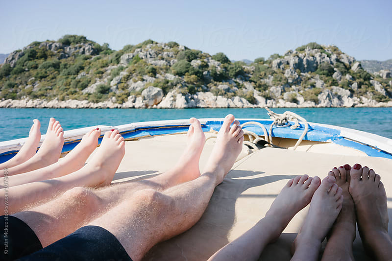 Family's feet while lying on boat in Mediterranean by Kirstin Mckee for Stocksy United
