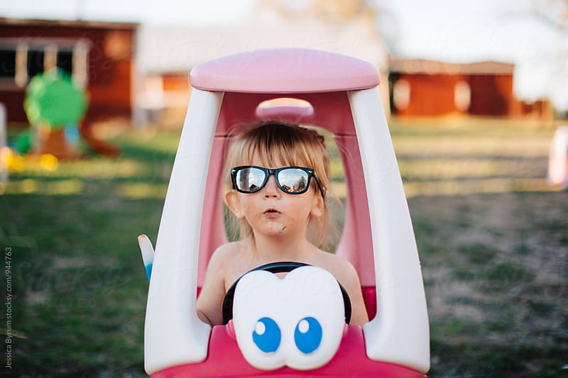 Little girl making a funny face in pink toy car by Jessica Byrum for Stocksy United