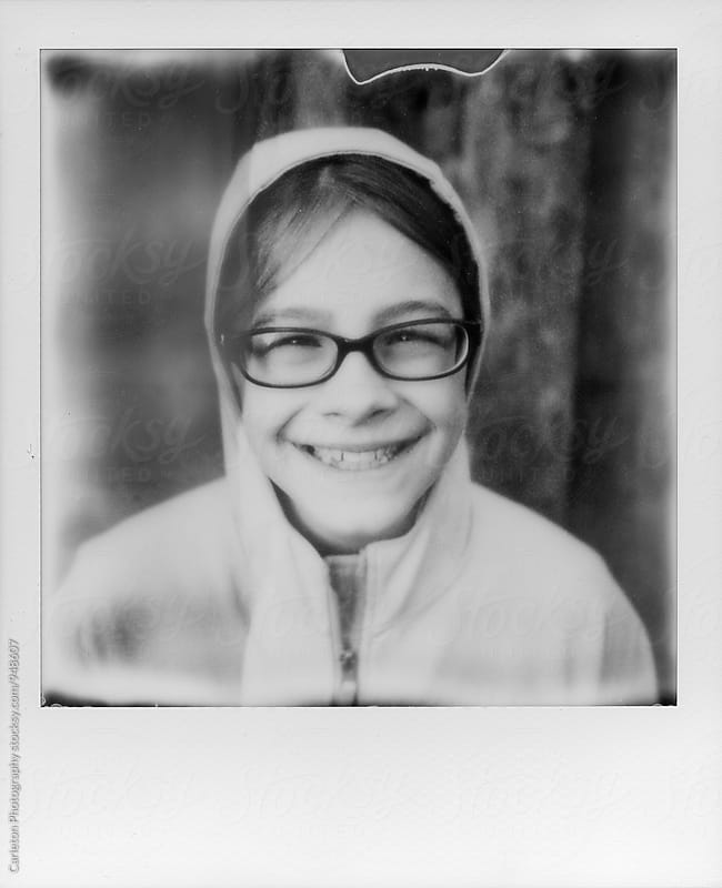Instant film photo of a smiling girl in glasses by Carleton Photography for Stocksy United