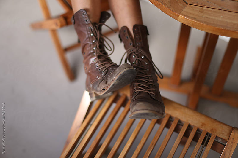 Dirty boots and legs on a wooden chair. by Painted Wood for Stocksy United