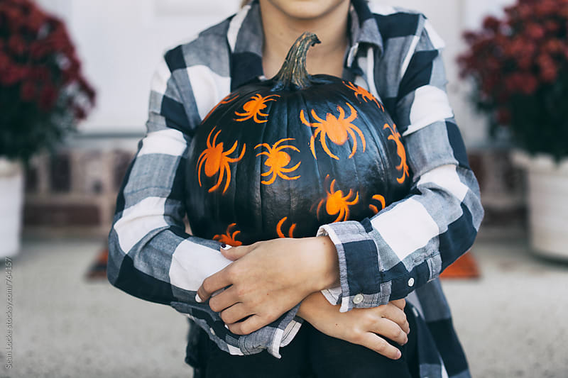 Painted: Sitting Teen Girl Holds Black Spider Pumpkin by Sean Locke for Stocksy United