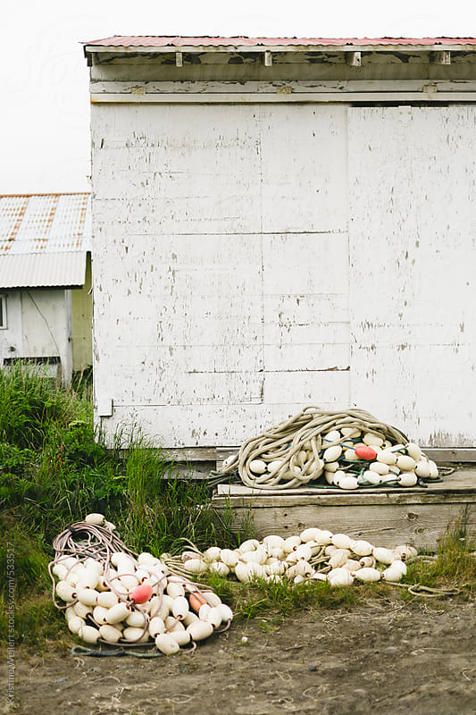 Old fishing nets sitting outside a white shack by Kristine Weilert for Stocksy United