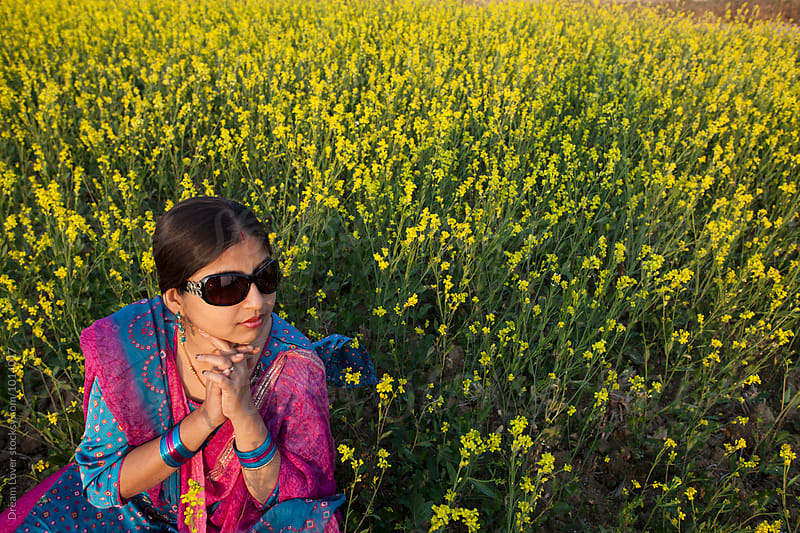 Indian woman in a mustard field by PARTHA PAL for Stocksy United