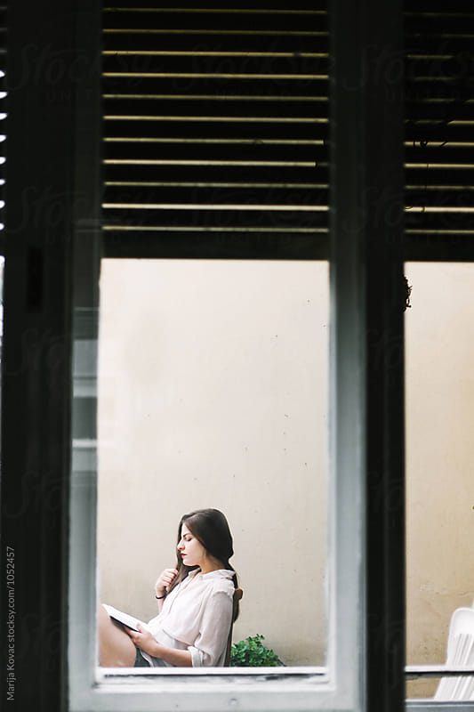 Brunette woman reading a book, through the window by Marija Kovac for Stocksy United